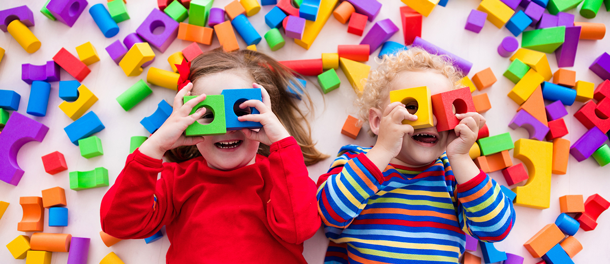 Children playing with colorful blocks building a block tower