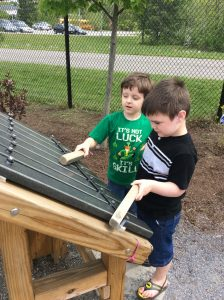 Boys playing on giant zylophone